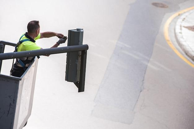 Trabalhador reparando as lâmpadas de um semáforo até um guindaste na estrada