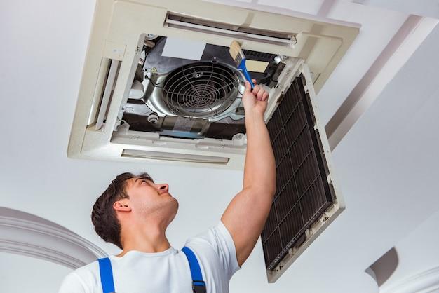 Trabalhador reparando unidade de ar condicionado de teto