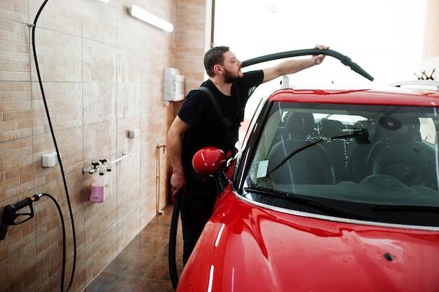 Trabalhador secando carro vermelho na garagem de detalhes após a lavagem