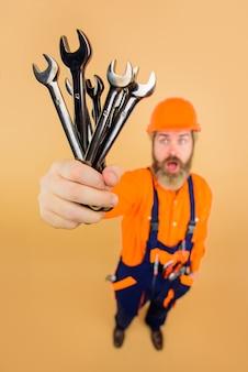 Trabalhador segura chaves inglesas chaves inglesas ferramentas de reparos construção indústria tecnologia chave inglesa construtor barbudo