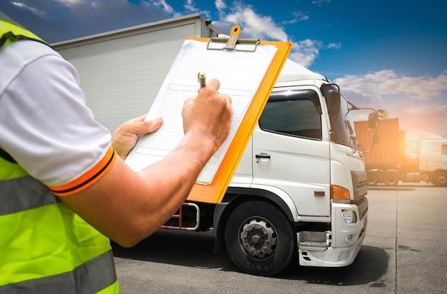 Trabalhador segurando a área de transferência seu controle de carregamento de carga no armazém.