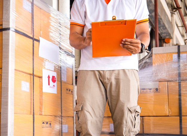 Trabalhador segurando a prancheta, fazendo gerenciamento de estoque no armazém de armazenamento, remessa, verificar estoque