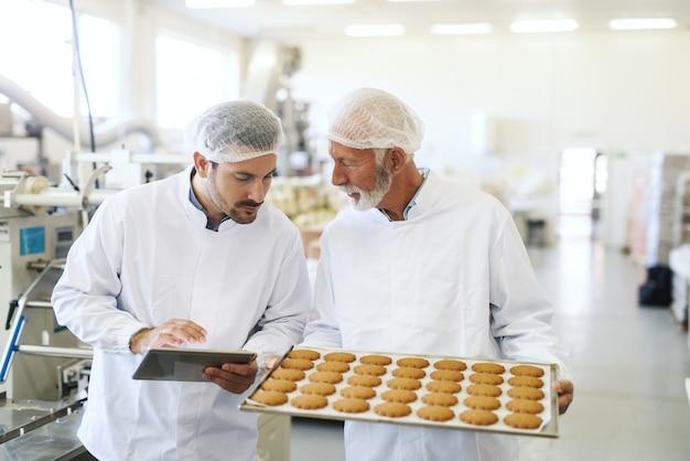 Trabalhador segurando caçarola com biscoitos enquanto o supervisor verifica a qualidade e segura o tablet. interior da fábrica de alimentos.