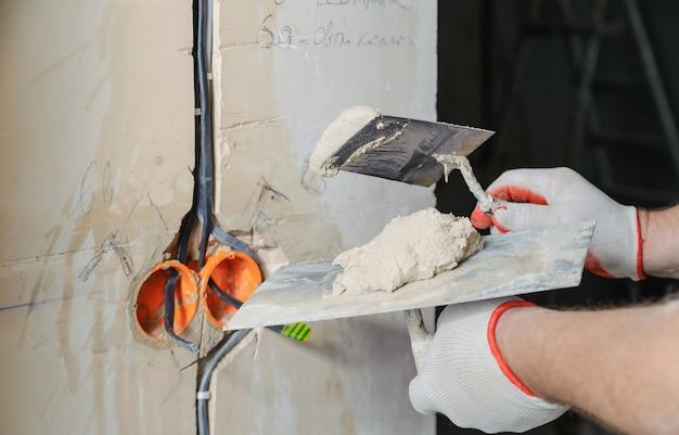 Trabalhador segurando espátulas com gesso cobrindo os cabos elétricos na parede