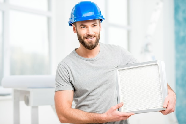 Trabalhador segurando filtro de ar para instalação no sistema de ventilação da casa. pureza do conceito de ar