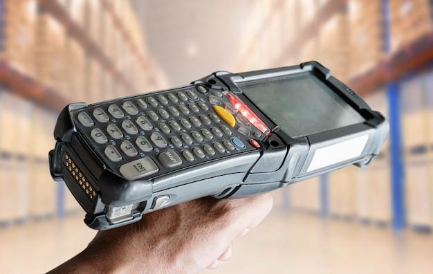 Trabalhador segurando o scanner de código de barras com depósito de armazenamento turva. ferramenta informática para gestão de inventário.