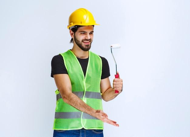 Trabalhador segurando um rolo aparador branco para pintura de parede.