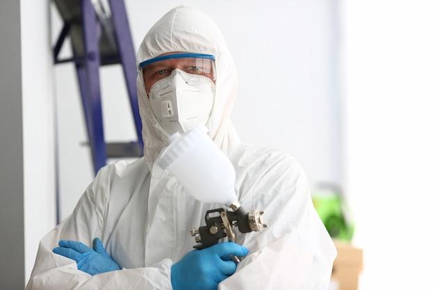 Trabalhador segurar na pistola de aerógrafo de braço vestindo traje de proteção