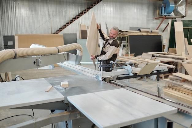 Trabalhador sênior da fábrica de móveis de uniforme, colocando uma grande placa de madeira pesada na máquina industrial antes de processá-la