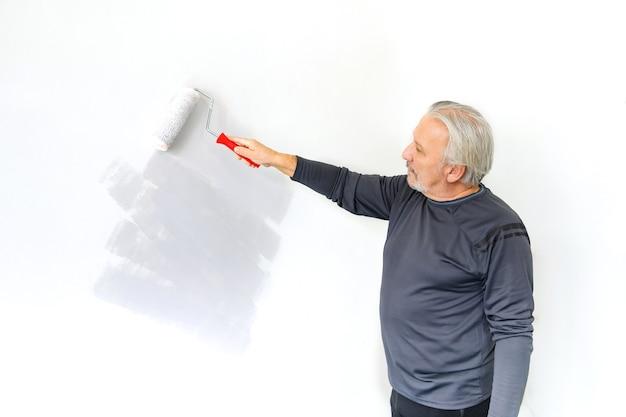 Trabalhador sênior usando rolo de âncora na parede. interior do apartamento de pintura do homem sênior.
