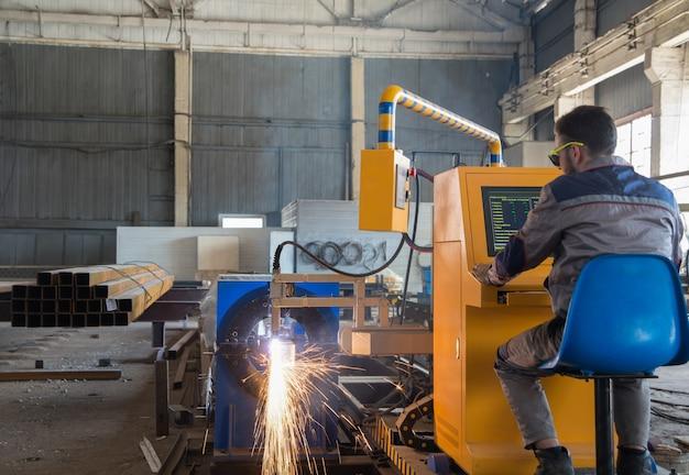 Trabalhador sentado atrás de uma máquina de solda a gás de controle remoto. sistema de corte de tubo