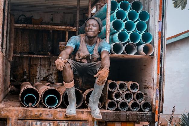 Trabalhador sentado em tubos enferrujados