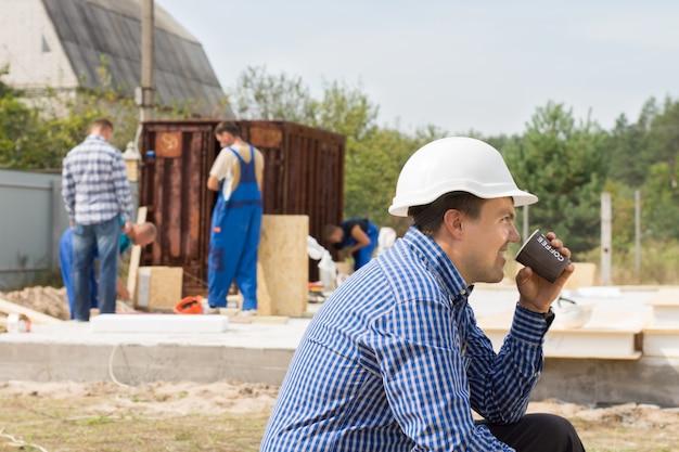 Trabalhador sentado relaxando tomando café em um canteiro de obras enquanto seus colegas continuam trabalhando, vista lateral em um capacete de segurança