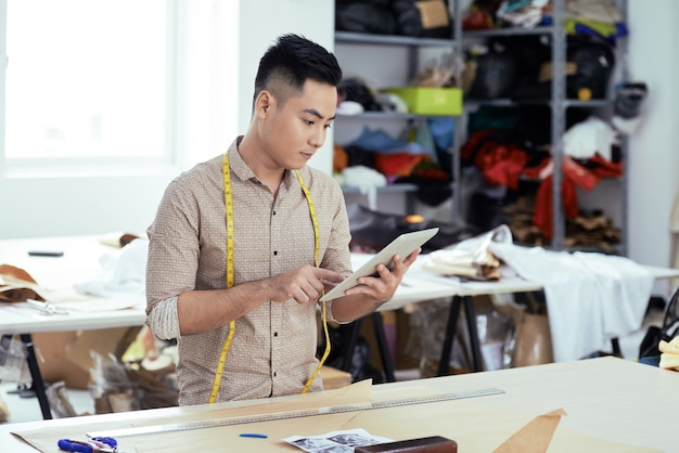 Trabalhador sério na fabricação de roupas verificando novos padrões no computador tablet