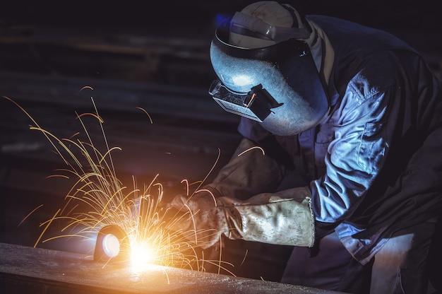 Trabalhador solda estrutura de aço na fábrica