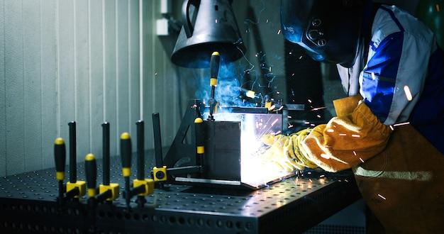 Trabalhador solda na fábrica trabalhando na indústria de metal