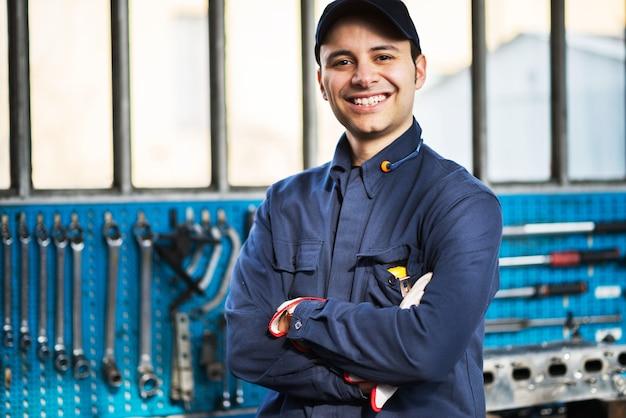 Trabalhador sorridente na frente de suas ferramentas