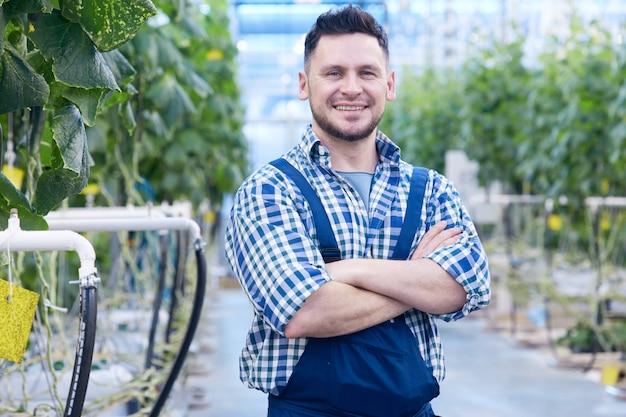 Trabalhador sorridente na plantação de vegetais