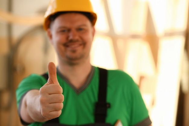 Trabalhador sorridente no capacete amarelo mostrando sinal ok