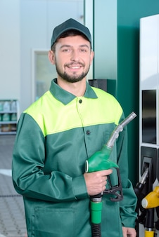 Trabalhador sorridente no posto de gasolina, enquanto encher um carro