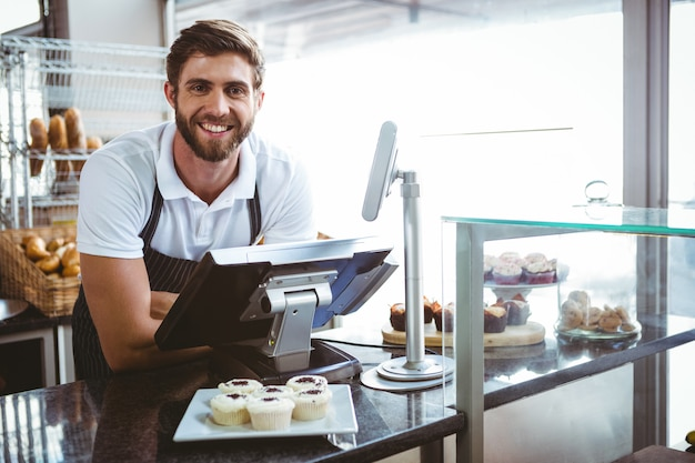 Trabalhador sorridente posando atrás do balcão