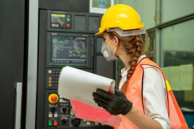 Trabalhador técnico feminino trabalhando e verificando a máquina em uma grande fábrica industrial