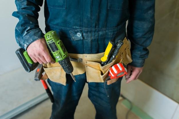 Trabalhador tem ferramentas de construção em suas mãos.