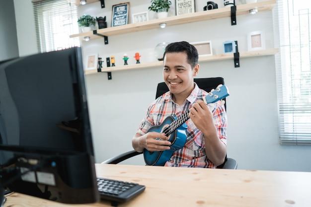 Trabalhador, tocando com seu violão enquanto olha para o computador