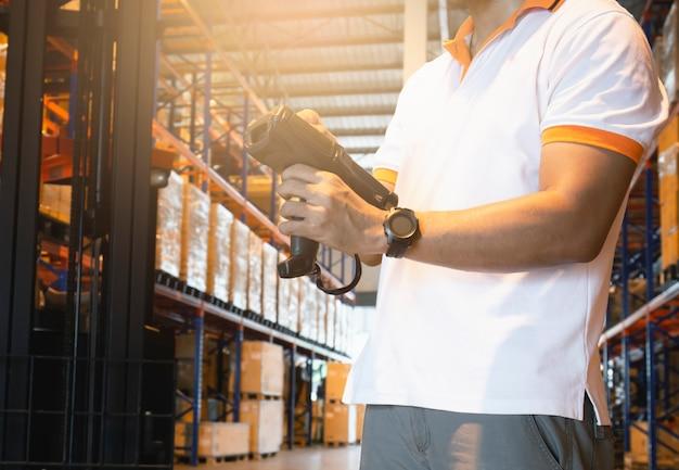 Trabalhador tocando na tela do scanner de código de barras. equipamento informático para gestão de inventário em armazém.