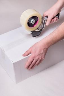 Trabalhador trabalha com dispensador de fita, fechando a caixa industrial de papelão, vertical