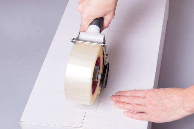 Trabalhador trabalha com dispensador de fita, fechando a caixa industrial de papelão