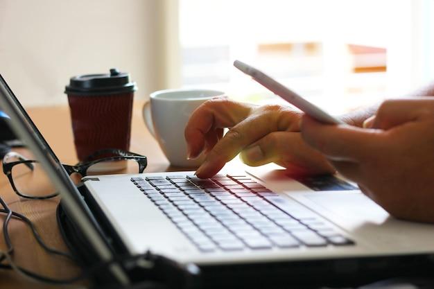 Trabalhador trabalha em casa com laptop e usando o celular, ligando para sua equipe no escritório Foto Premium