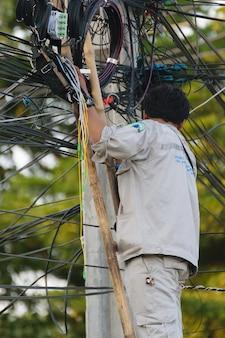 Trabalhador trabalhando para instalar o sistema de fibra de internet