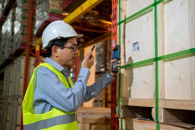 Trabalhador trabalhando usar rádio para se comunicar no grande armazém, atacado, logística, pessoas e conceito de exportação.
