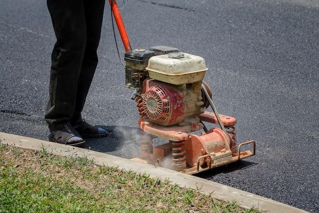Trabalhador usa compactador de placa vibratória para compactar asfalto na reparação de estradas