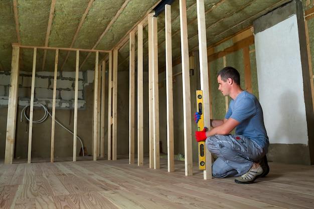 Trabalhador usa nível instalar moldura de madeira para futuras paredes.