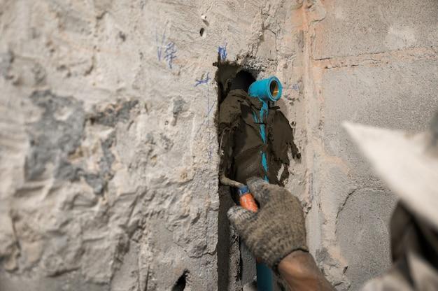 Trabalhador usando espátula, rebocando cimento em parede deteriorada com cano de água de pvc em banheiro reformado