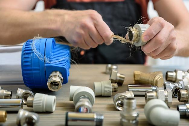 Trabalhador usando fibras de cânhamo de um encanador para selar juntas de tubos