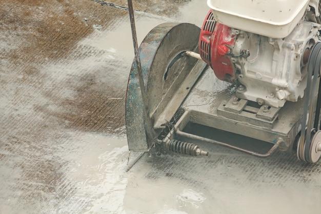 Trabalhador usando máquina de lâmina de serra de diamante cortando estrada de concreto no canteiro de obras