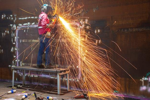 Trabalhador usando moagem de faísca de roda elétrica em placa de concha de peça de aço carbono de metal de soldador dentro do espaço confinado do tanque
