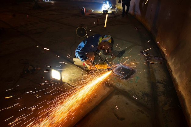 Trabalhador usando moagem de faísca de roda elétrica na placa inferior da peça de aço carbono de metal do soldador dentro do espaço confinado do tanque