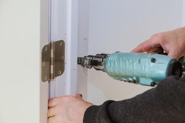 Trabalhador usando pistola de pregos brad instala portas carpinteiro usando uma pistola de pregos arma de ar para pistola de pregos