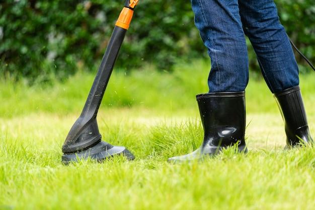 Trabalhador usando um cortador de grama cortando grama em casa