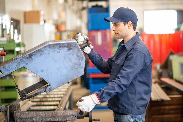 Trabalhador usando um cortador para cortar um tubo de ferro em uma fábrica