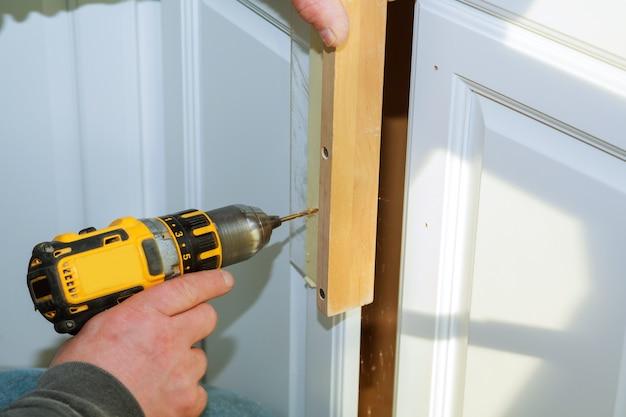 Trabalhador usar broca para reparar móveis e perfura a porta do armário