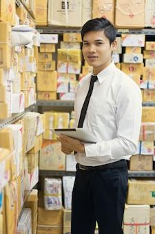 Trabalhador, verificando o pacote no armazém.
