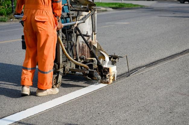 Trabalhador vestindo uniforme está fazendo a linha branca na estrada com máquina de pintura