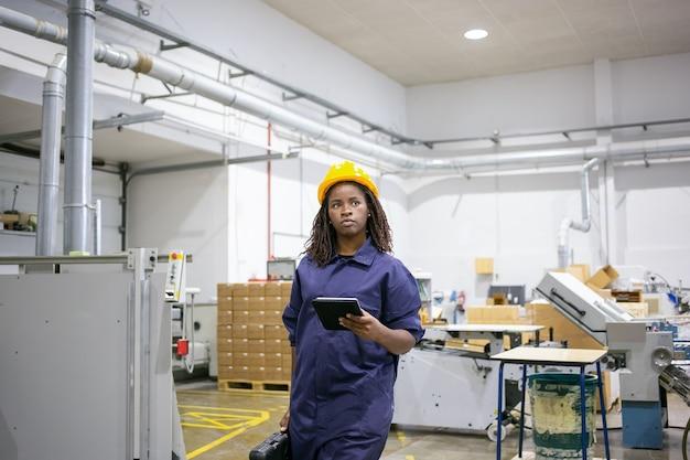 Trabalhadora afro-americana séria com uniforme de proteção, caminhando para o local de trabalho no chão da fábrica, segurando o tablet e a caixa com ferramentas