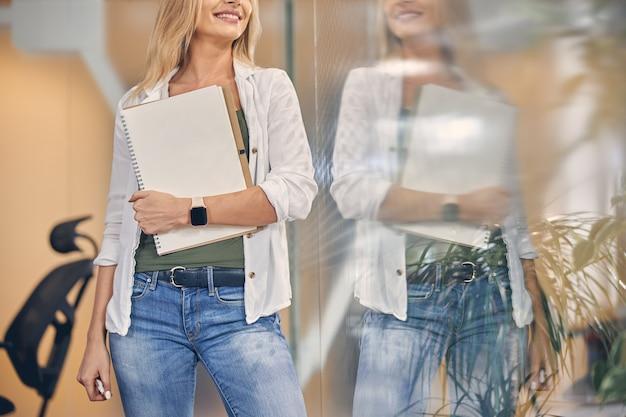 Trabalhadora alegre em roupa casual segurando um caderno de desenho em espiral e sorrindo