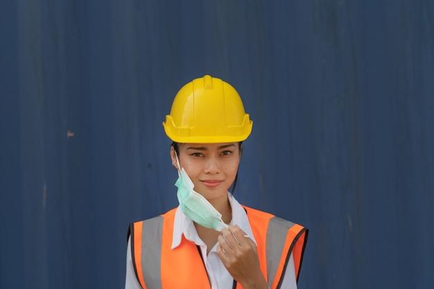 Trabalhadora asiática na parede azul segurando a máscara